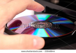 stock-photo-inserting-a-disc-into-a-dvd-or-cd-player-23048644